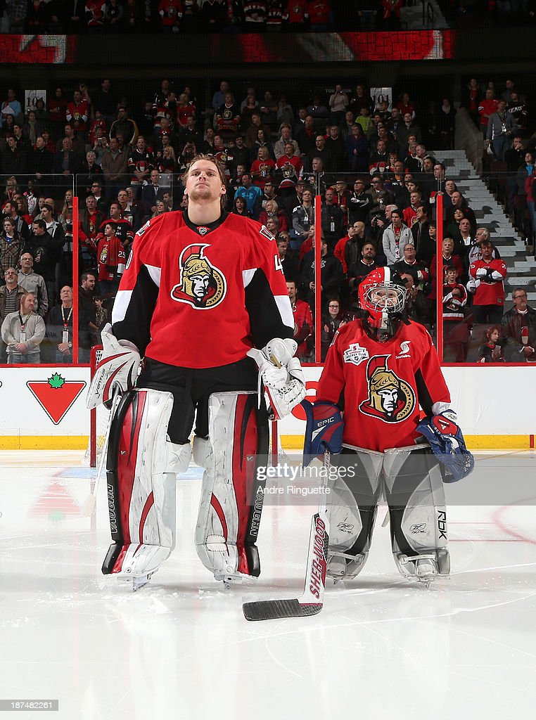 Robin Lehner #40 of the Ottawa Senators stands during the singing of the national anthems with a minor hockey player prior to a game against the Florida Panthers to kick off Minor Hockey Week at Canadian Tire Centre on November 9, 2013 in Ottawa, Ontario, Canada.