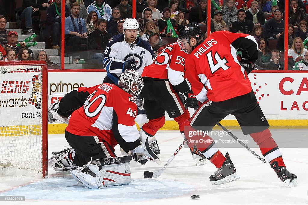 Robin Lehner #40 of the Ottawa Senators watches the loose puck go past teammate Chris Phillips #4 as Andrew Ladd #16 of the Winnipeg Jets looks on, during an NHL game at Scotiabank Place on March 17, 2013 in Ottawa, Ontario, Canada.