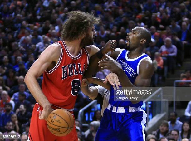 Robin Lopez of the Chicago Bulls fights with Serge Ibaka of the Toronto Raptors during the second half of an NBA game at Air Canada Centre on March...