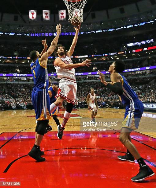 Robin Lopez of the Chicago Bulls shoots between JaVale McGee and Patrick McCaw of the Golden State Warriors at the United Center on March 2 2017 in...