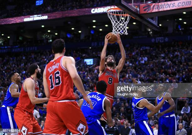 Robin Lopez of the Chicago Bulls shoots the ball as DeMar DeRozan of the Toronto Raptors defends during the second half of an NBA game at Air Canada...