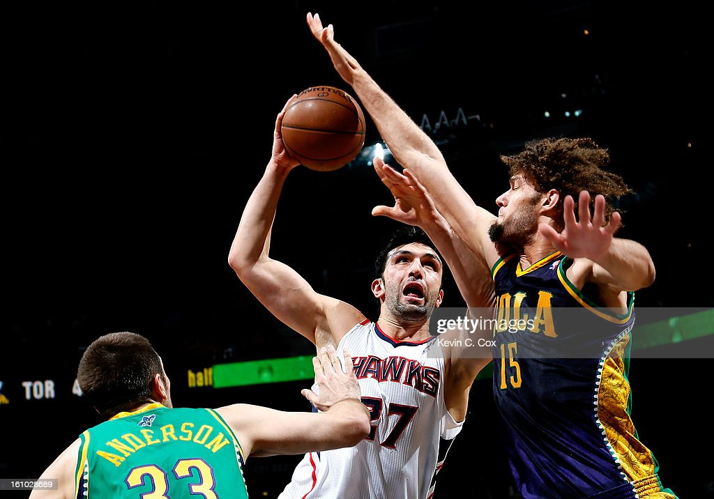 Robin Lopez #15 of the New Orleans Hornets blocks a shot by Zaza Pachulia #27 of the Atlanta Hawks at Philips Arena on February 8, 2013 in Atlanta, Georgia.