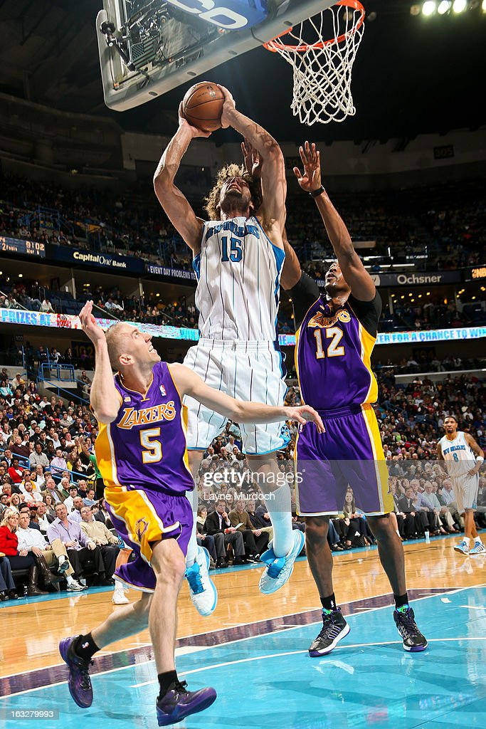 Robin Lopez #15 of the New Orleans Hornets drives to the basket against Dwight Howard #12 and Steve Blake #5 of the Los Angeles Lakers on March 6, 2013 at the New Orleans Arena in New Orleans, Louisiana.