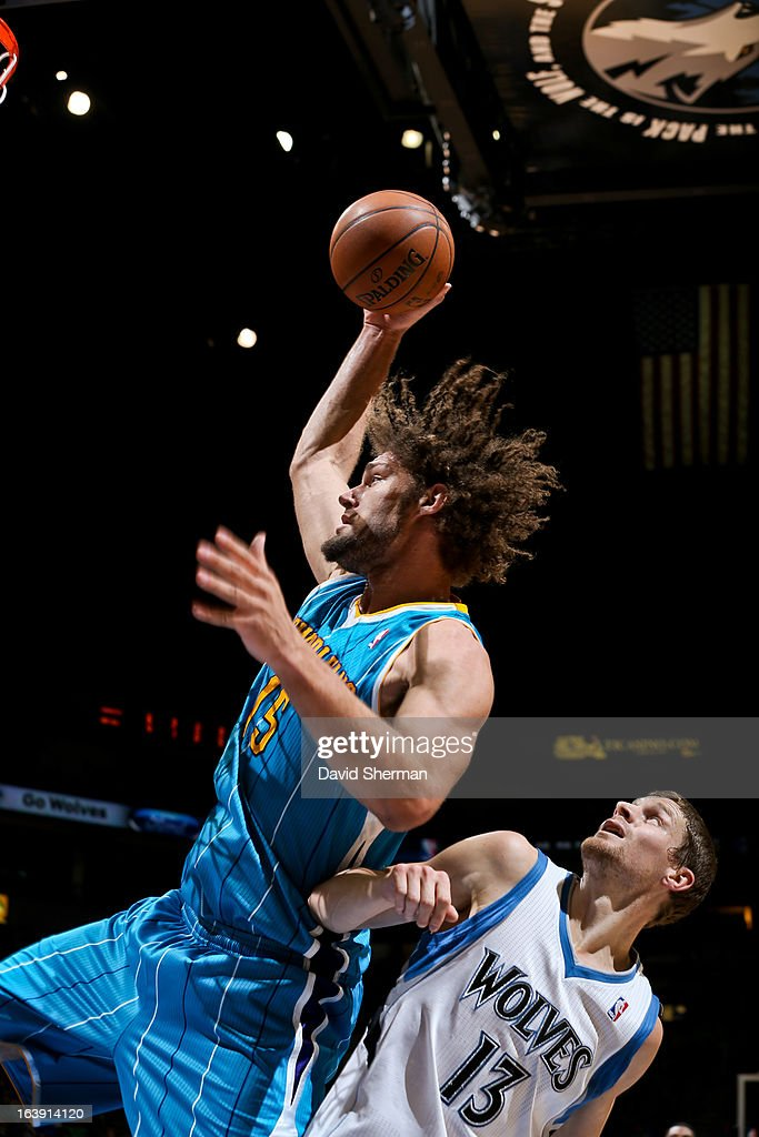 Robin Lopez #15 of the New Orleans Hornets drives to the basket against Luke Ridnour #13 of the Minnesota Timberwolves on March 17, 2013 at Target Center in Minneapolis, Minnesota.