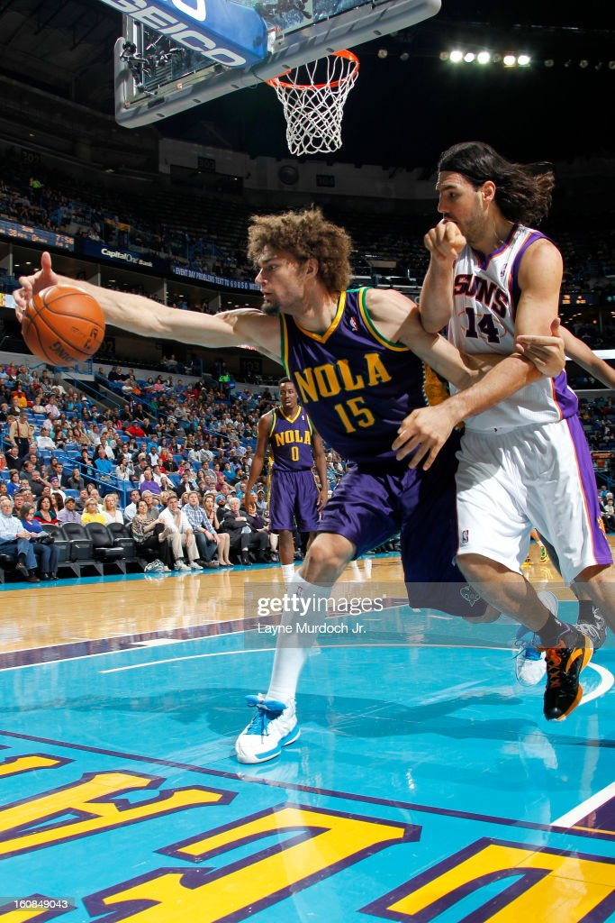 Robin Lopez #15 of the New Orleans Hornets saves the ball from going out of bounds against Luis Scola #14 of the Phoenix Suns on February 06, 2013 at the New Orleans Arena in New Orleans, Louisiana.