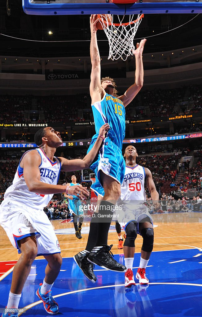Robin Lopez #15 of the New Orleans Hornets shoots a layup against Evan Turner #12 and Lavoy Allen #50 of the Philadelphia 76ers during the game at the Wells Fargo Center on January 15, 2013 in Philadelphia, Pennsylvania.