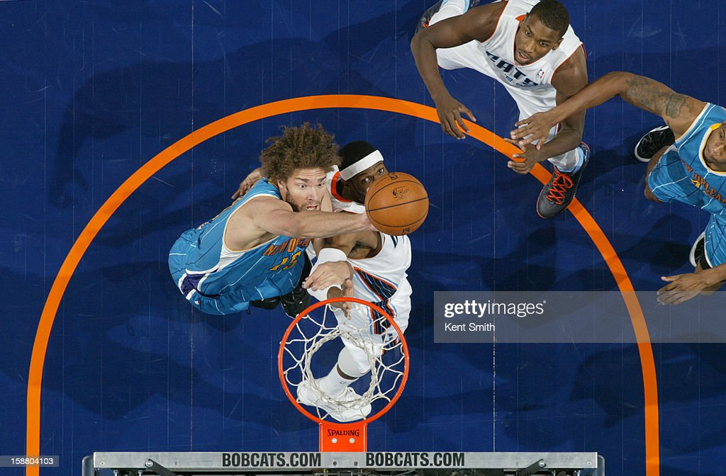 Robin Lopez #15 of the New Orleans Hornets taps in the shot against Brendan Haywood #33 of the Charlotte Bobcats at the Time Warner Cable Arena on December 29, 2012 in Charlotte, North Carolina.
