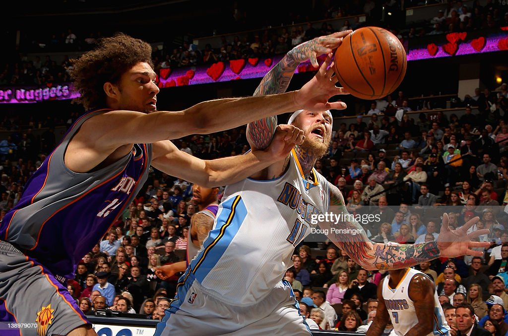 Robin Lopez of the Phoenix Suns and Chris Andersen of the Denver Nuggets vie for a loose ball at the Pepsi Center on February 14 2012 in Denver...