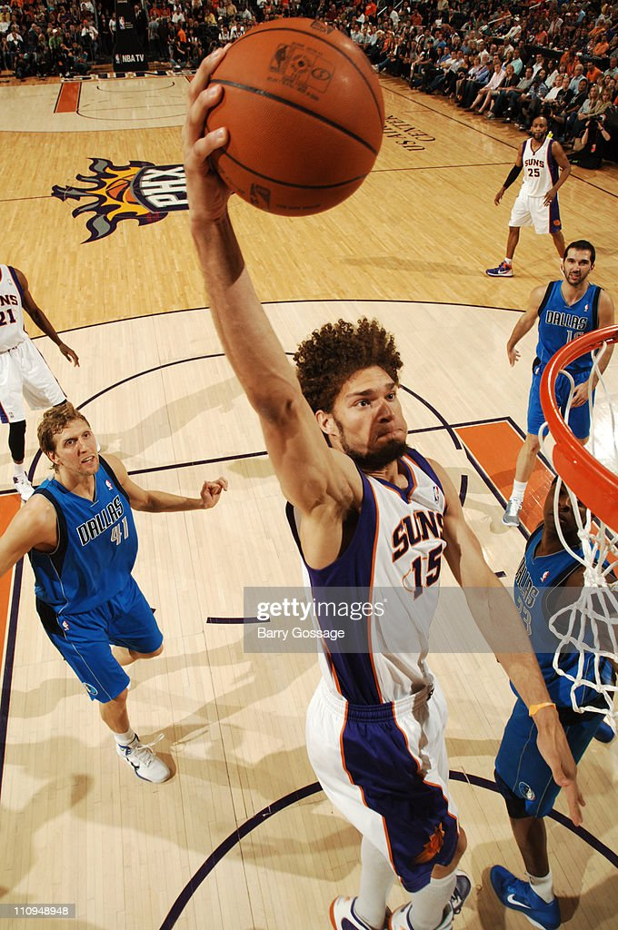 Robin Lopez of the Phoenix Suns drives for a dunk past Dirk Nowitzki of the Dallas Mavericks in an NBA game played on March 27 2011 at US Airways...