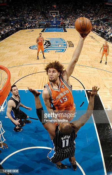 Robin Lopez of the Phoenix Suns goes to the basket against Glen Davis of the Orlando Magic during the game on March 21 2012 at Amway Center in...