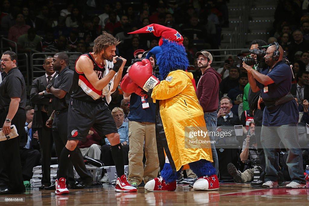 Robin Lopez of the Portland Trail Blazers pretends to box mascot GWiz of the Washington Wizards on March 16 2015 at the Verizon Center in Washington...