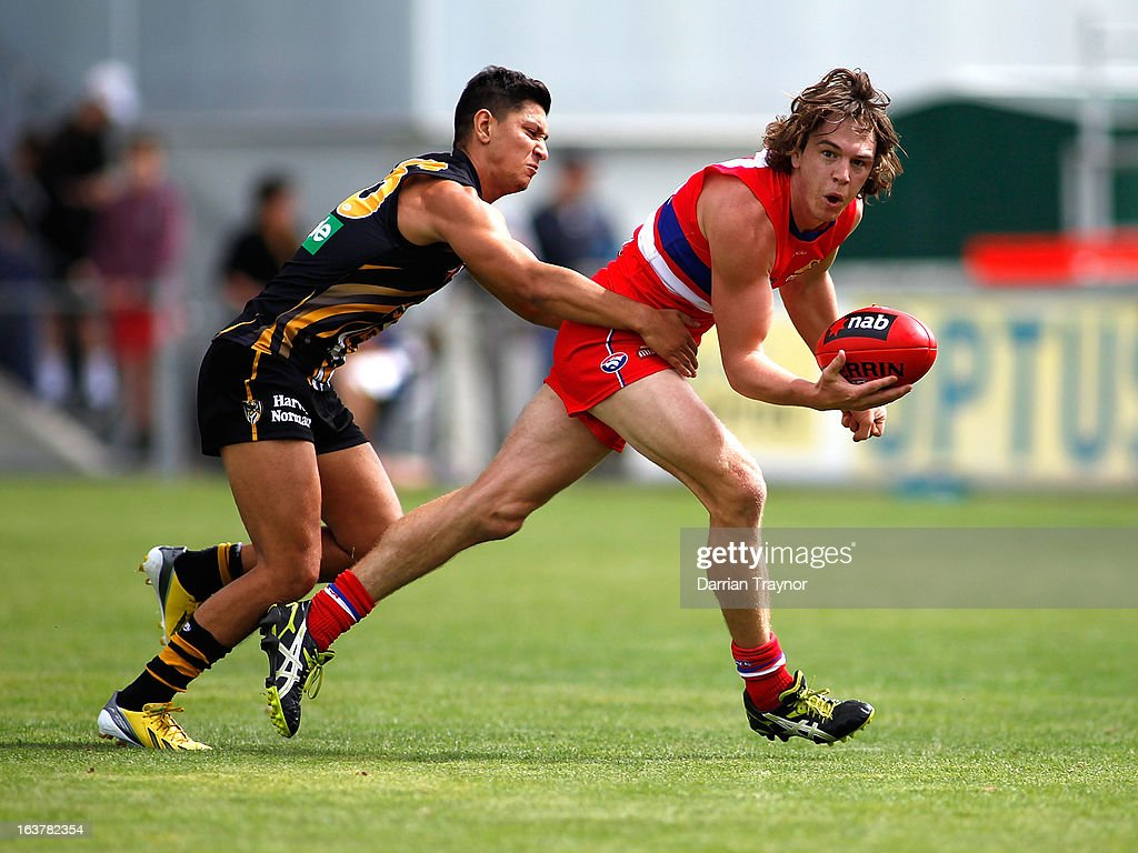 Robin Nahas of the Tigers attempts to tackle Liam Picken of the Bulldogs during the AFL practice match between the Richmond Tigers and the Western Bulldogs at Visy Park on March 16, 2013 in Melbourne, Australia.