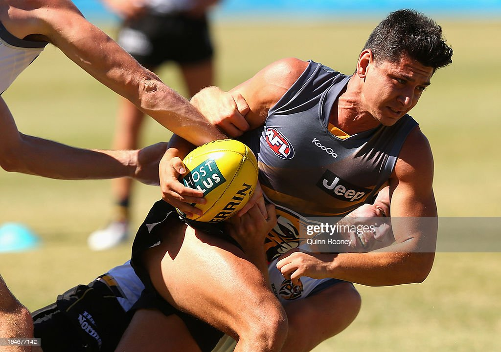 Robin Nahas of the Tigers handballs whilst being tackled during a Richmond Tigers AFL training session at ME Bank Centre on March 26, 2013 in Melbourne, Australia.
