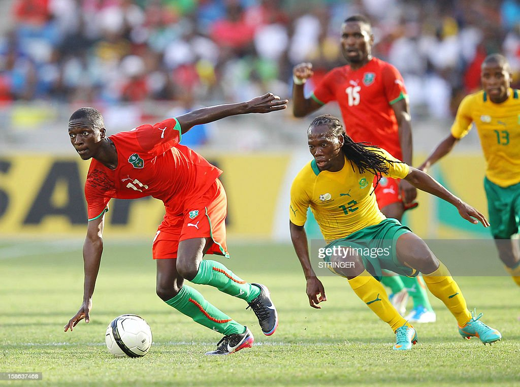 Robin Ngalande of Malawi (L) beats Renielwe Letsholonyane of South Africa to the ball during the International friendly match between South Africa and Malawi from Moses Mabhida Stadium on December 22, 2012 in Durban, South Africa, one month before South Africa host the Orange Africa Cup of Nations, CAN
