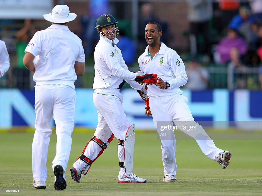 Robin Peterson (R) and AB de Villiers of South Africa celebrates on January 12, 2013 the wicket of New Zealand's Brendon McCullum on the second day of the second and final Test between South Africa and New Zealand at St George's Park in Port Elizabeth. AFP PHOTO / Anesh Debiky