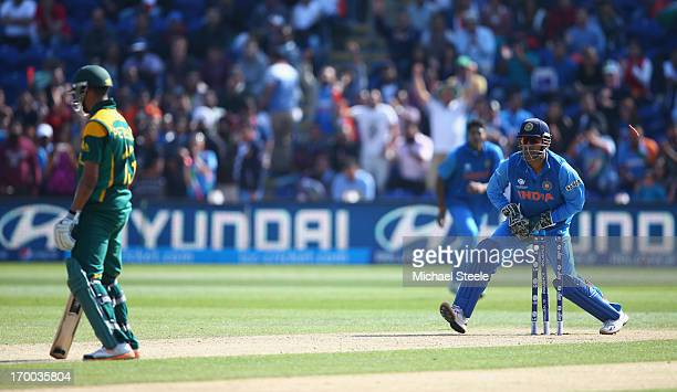 Robin Peterson of South Africa is left stranded after a mix up with AB de Villiers and is run out by MS Dhoni of India during the Group B ICC...