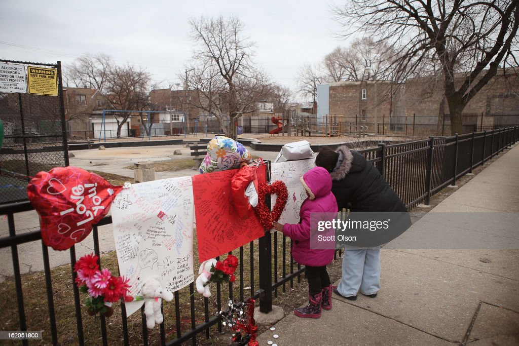 Robin Pettus and her daughter Aletha sign a memorial to their eighteen-year-old cousin Frances Colon near the spot where she was murdered on February 18, 2013 in Chicago, Illinois. Colon, who was shot February 15th while walking by the neighborhood play lot, was the 51st person murdered in Chicago in 2013. She was the third student from Roberto Clemente High School, a Westside school with less than 800 students, to be murdered in the past three months.