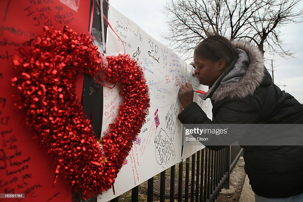 Robin Pettus signs a memorial to her eighteen-year-old cousin Frances Colon near the spot where she was murdered on February 18, 2013 in Chicago, Illinois. Colon, who was shot February 15th while walking by a neighborhood play lot, was the 51st person murdered in Chicago in 2013. She was the third student from Roberto Clemente High School, a Westside school with less than 800 students, to be murdered in the past three months.