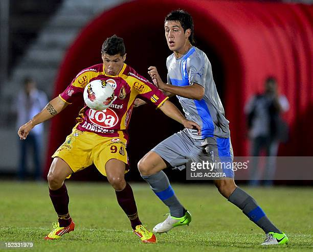 Robin Ramirez of Colombia's Deportes Tolima vies for the ball with Enzo Andia of Chile's Universidad Catolica during their 2012 Copa Sudamericana...