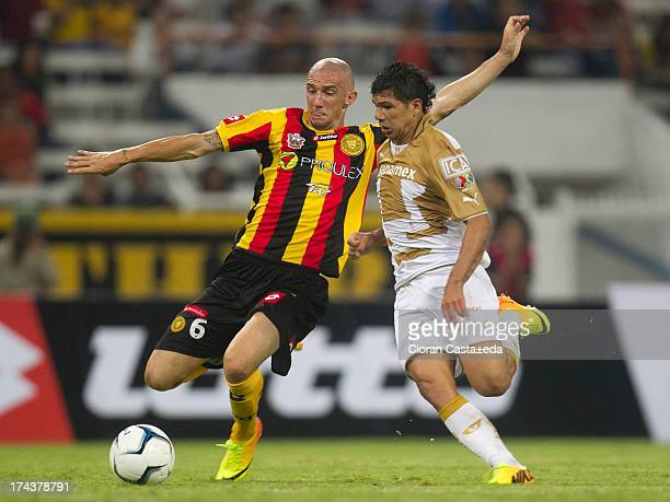 Robin Ramirez of Pumas competes for the ball with Rodrigo Folle of Leones Negros during a match between Leones Negros and Pumas as part of the Cup MX...