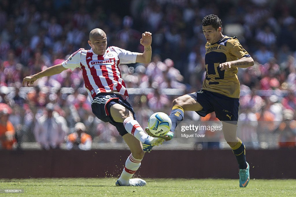 Robin Ramirez of Pumas, fights for the ball with <a gi-track='captionPersonalityLinkClicked' href=/galleries/search?phrase=Jorge+Enriquez&family=editorial&specificpeople=6623957 ng-click='$event.stopPropagation()'>Jorge Enriquez</a> of Chivas during a match between Pumas and Chivas as part of the Clausura 2013 at Olympic stadium on March 03, 2013 in Mexico City, Mexico.