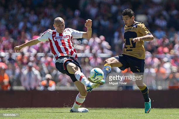 Robin Ramirez of Pumas fights for the ball with Jorge Enriquez of Chivas during a match between Pumas and Chivas as part of the Clausura 2013 at...
