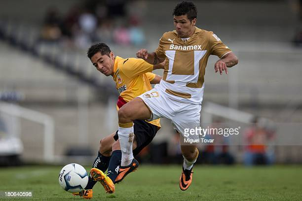Robin Ramirez of Pumas fights for the ball with Jose Maria Cardenas of Morelia during a match between Pumas and Morelia as part of the Apertura 2013...
