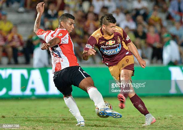 Robin Ramirez of Tolima kicks the ball as Luis Narvaez of Junior tries to defend during a first leg match between Deportes Tolima and Atletico Junior...