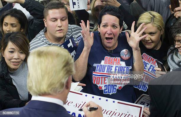 Robin Roy screams as she has her poster signed by US Republican Presidential Candidate Donald Trump during a campaign rally at the UMass Tsongas...