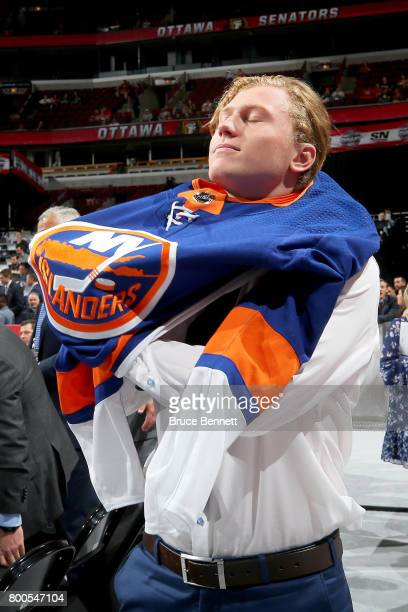 Robin Salo puts on the New York Islanders jersey after being selected 46th overall during the 2017 NHL Draft at the United Center on June 24 2017 in...