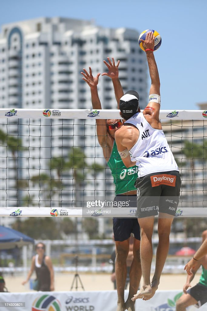 Robin Seidl of Austria spikes the ball over Kvamsdal Morten of Norway at the ASICS World Series of Beach Volleyball - Day 2 on July 23, 2013 in Long Beach, California.