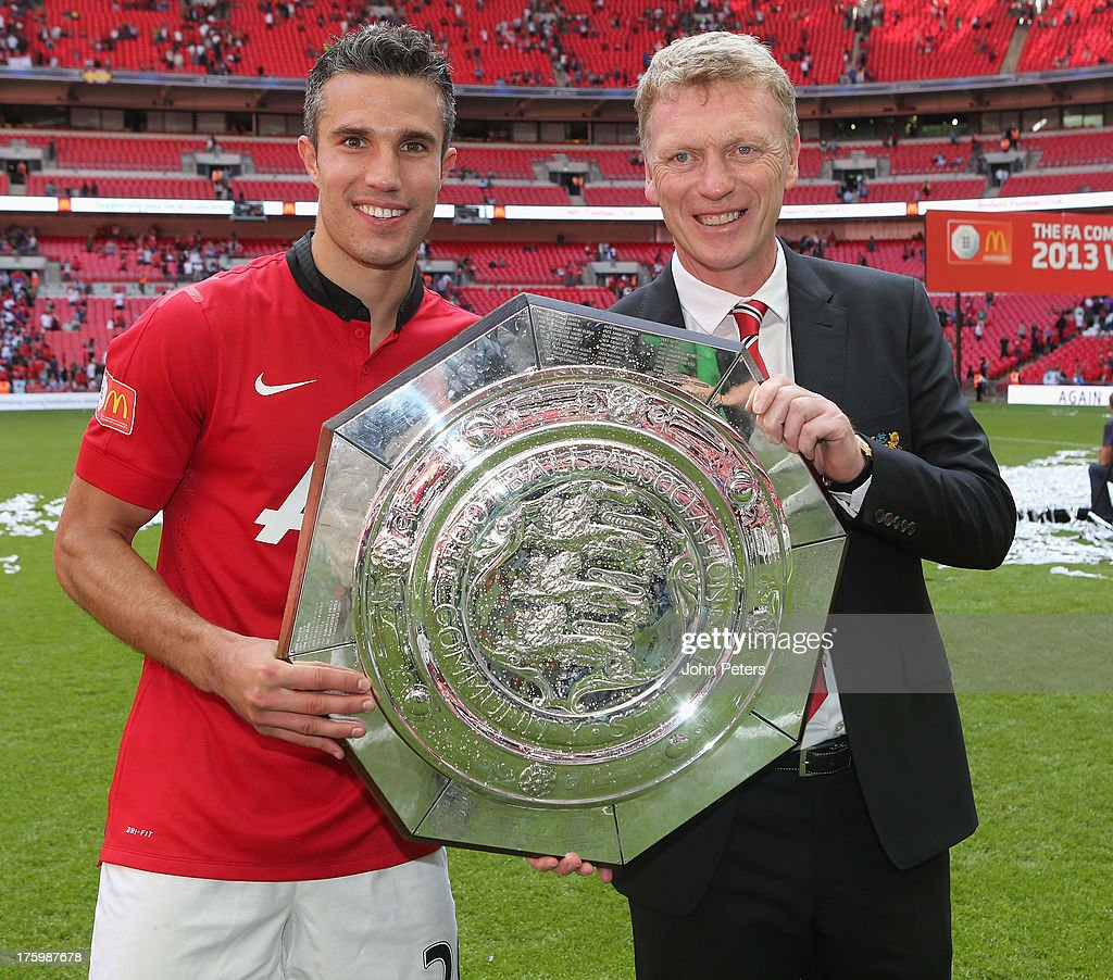 Robin van Persie and Manager <a gi-track='captionPersonalityLinkClicked' href=/galleries/search?phrase=David+Moyes&family=editorial&specificpeople=215482 ng-click='$event.stopPropagation()'>David Moyes</a> of Manchester United pose with the FA Community Shield trophy after the FA Community Shield match between Manchester United and Wigan Athletic at Wembley Stadium on August 11, 2013 in London, England.