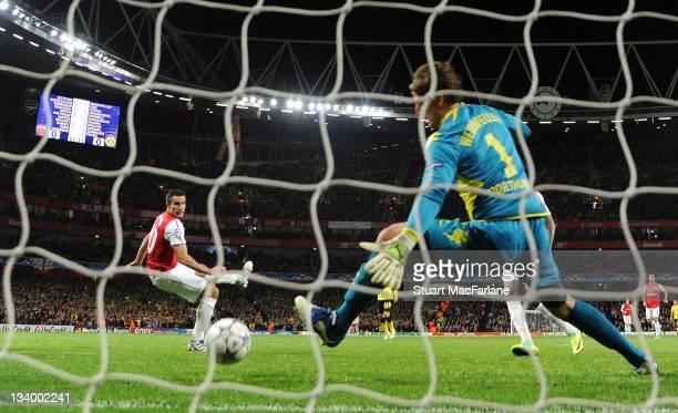Robin van Persie heads past Dortmund goalkeeper Roman Weidenfeller to score the 1st Arsenal goal during the UEFA Champions League Group F match...