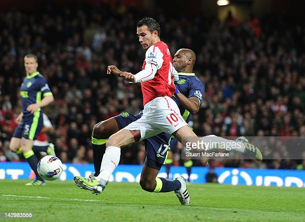 Robin van Persie of Arsenal breaks past Emmerson Boyce of Wigan during the Barclays Premier League match between Arsenal and Wigan Athletic at...
