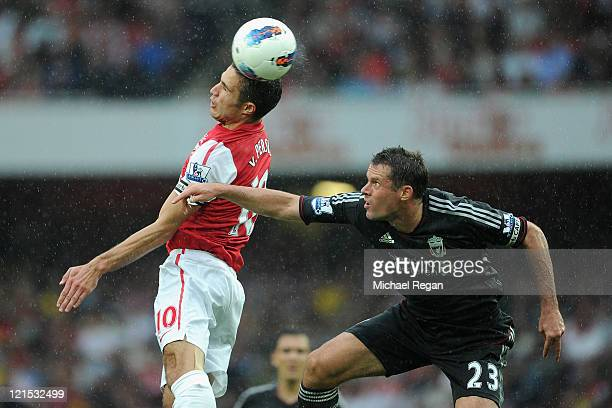 Robin van Persie of Arsenal heads the ball as Jamie Carragher of Liverpool looks on during the Barclays Premier League match between Arsenal and...