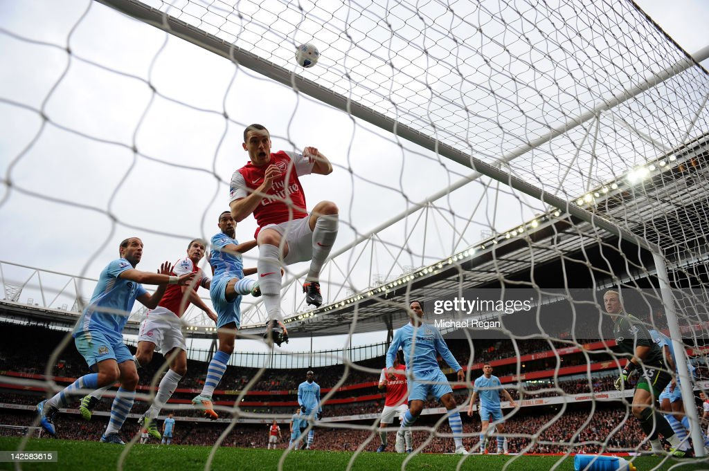Robin van Persie of Arsenal's shot at goal hits Thomas Vermaelen of Arsenal in the face and goes over the bar during the Barclays Premier League...
