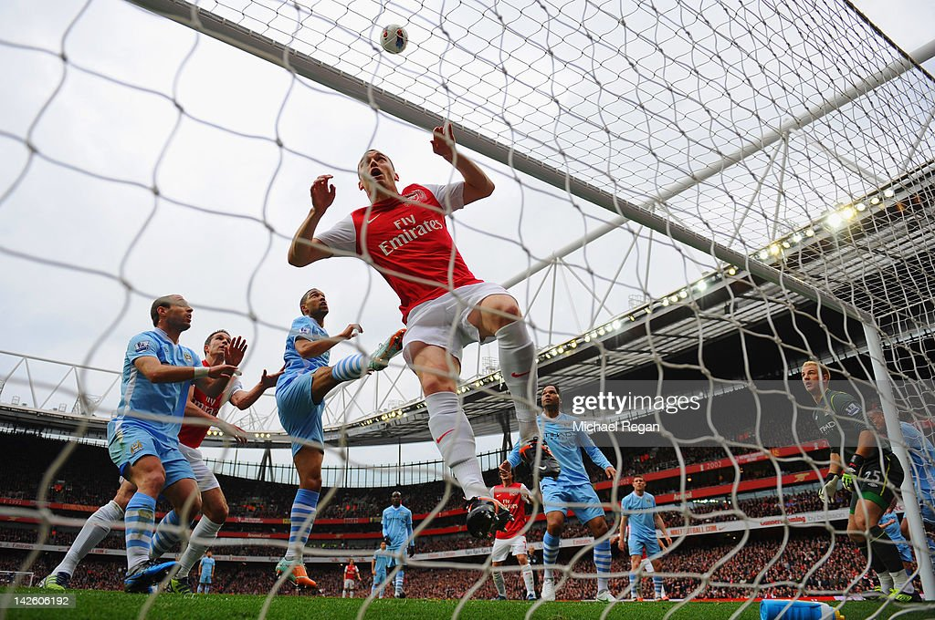 Robin van Persie of Arsenal's shot at goal hits Thomas Vermaelen of Arsenal in the face and goes over the bar during the Barclays Premier Match between Arsenal and Manchester City at the Emirates Stadium on April 8, 2012 in London, England.