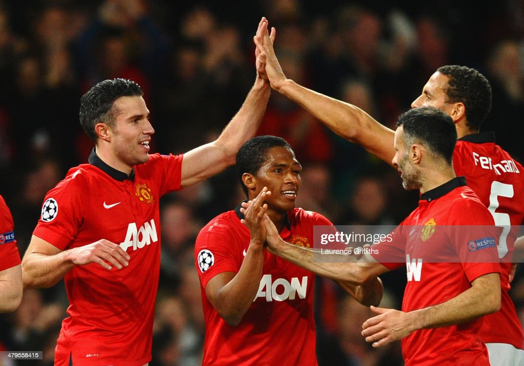 Robin van Persie of Manchester United celebrates scoring the second goal with his team-mates during the UEFA Champions League Round of 16 second round match between Manchester United and Olympiacos FC at Old Trafford on March 19, 2014 in Manchester, England.
