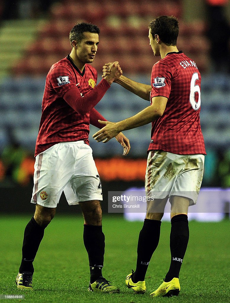 Robin Van Persie of Manchester United celebrates with team-mate Jonny Evans at full-time following the Barclays Premier League match between Wigan Athletic and Manchester United at DW Stadium on January 1, 2013 in Wigan, England.