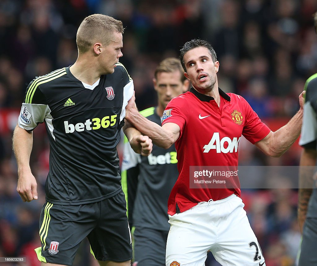 Robin van Persie of Manchester United clashes with <a gi-track='captionPersonalityLinkClicked' href=/galleries/search?phrase=Ryan+Shawcross&family=editorial&specificpeople=4443278 ng-click='$event.stopPropagation()'>Ryan Shawcross</a> of Stoke City during the Barclays Premier League match between Manchester United and Stoke City at Old Trafford on October 26, 2013 in Manchester, England.