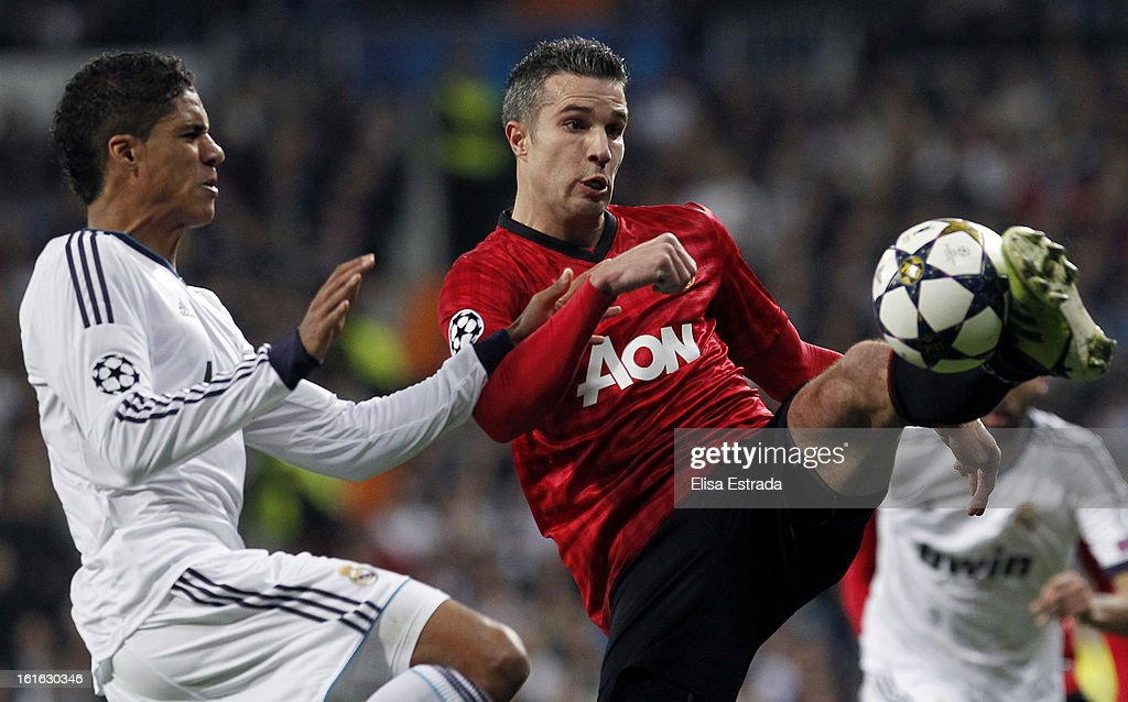 Robin van Persie (R) of Manchester United controls the ball in front of Raphael Varane of Real Madrid during the UEFA Champions League Round of 16 first leg match between Real Madrid and Manchester United at Estadio Santiago Bernabeu on February 13, 2013 in Madrid, Spain.