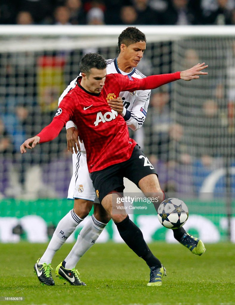 Robin van Persie of Manchester United controls the ball in front of Raphael Varane of Real Madrid during the UEFA Champions League Round of 16 first leg match between Real Madrid and Manchester United at Estadio Santiago Bernabeu on February 13, 2013 in Madrid, Spain.
