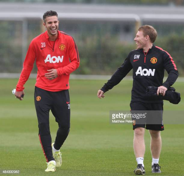 Robin van Persie of Manchester United in action with fitness coach Gary Walker during a first team training session at Aon Training Complex on August...