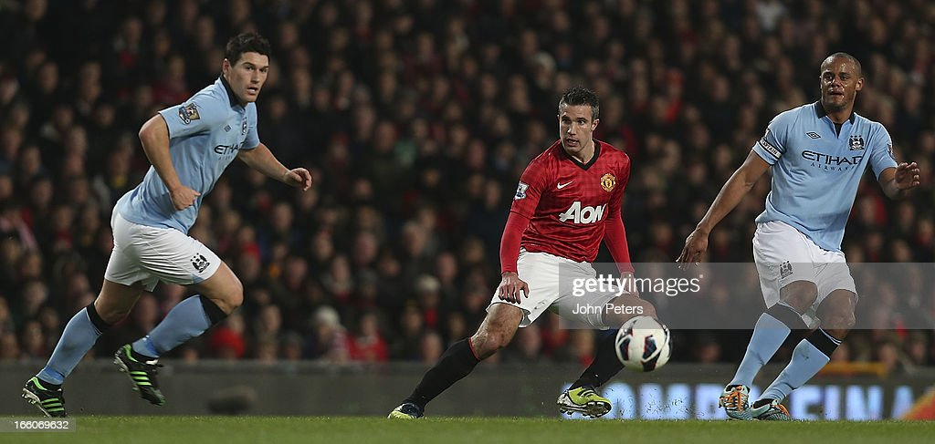 Robin van Persie of Manchester United in action with Gareth Barry (L) and Vincent Kompany of Manchester City during the Barclays Premier League match between Manchester United and Manchester City at Old Trafford on April 8, 2013 in Manchester, England.