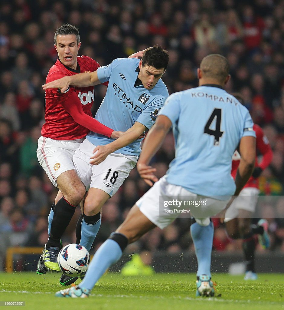 Robin van Persie of Manchester United in action with Gareth Barry of Manchester City during the Barclays Premier League match between Manchester United and Manchester City at Old Trafford on April 8, 2013 in Manchester, England.