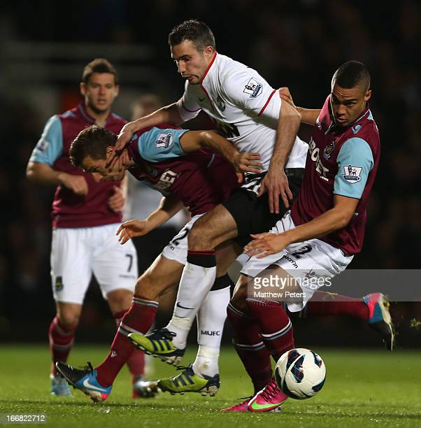 Robin van Persie of Manchester United in action with Gary O'Neil and Winston Reid of West Ham United during the Barclays Premier League match between...