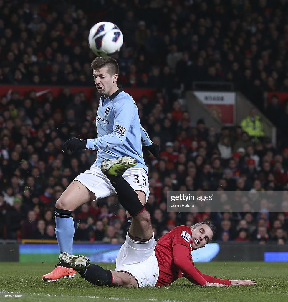 Robin van Persie of Manchester United in action with Matija Nastasic of Manchester City during the Barclays Premier League match between Manchester United and Manchester City at Old Trafford on April 8, 2013 in Manchester, England.