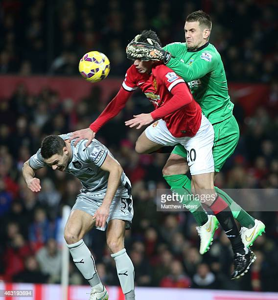 Robin van Persie of Manchester United in action with Michael Keane and Tom Heaton of Burnley during the Barclays Premier League match between...