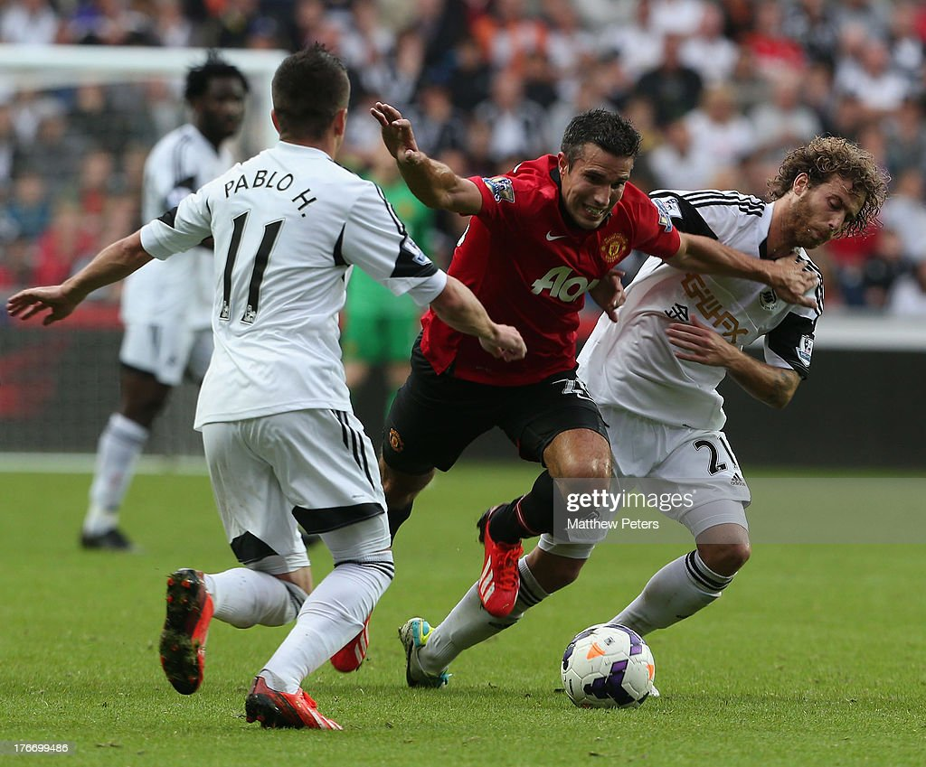 Robin van Persie of Manchester United in action with Pablo Hernandez (L) and Jose Canas of Swansea City during the Barclays Premier League match between Swansea City and Manchester United at the Liberty Stadium on August 17, 2013 in Swansea, Wales.