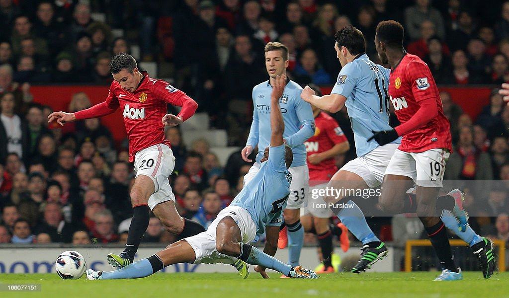 Robin van Persie of Manchester United in action with Vincent Kompany of Manchester City during the Barclays Premier League match between Manchester United and Manchester City at Old Trafford on April 8, 2013 in Manchester, England.